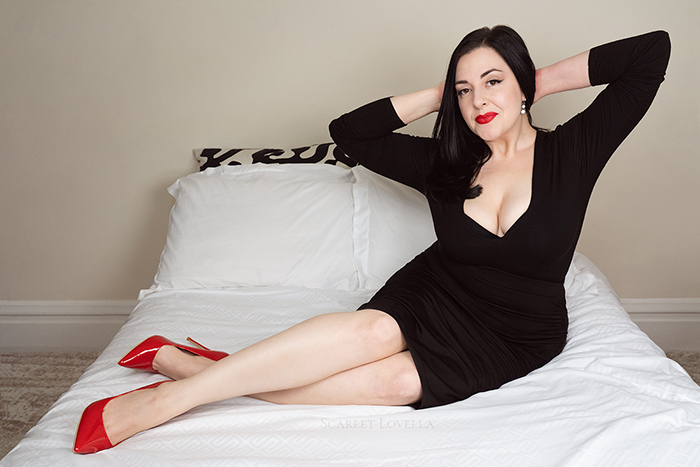 Scarlet Lovella lounging while wearing red high heels and red lipstick.